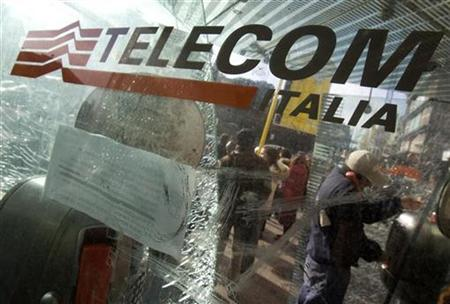 A man uses a Telecom Italia phone booth at a bus stop in Rome